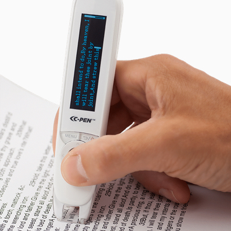 A hand holding a small device the size of a large pencil, scanning a book