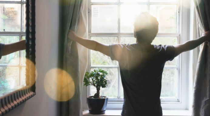 Man looking out the window with sunlight coming in