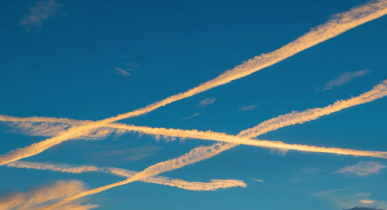 Blue sky with criss-crossing contrails