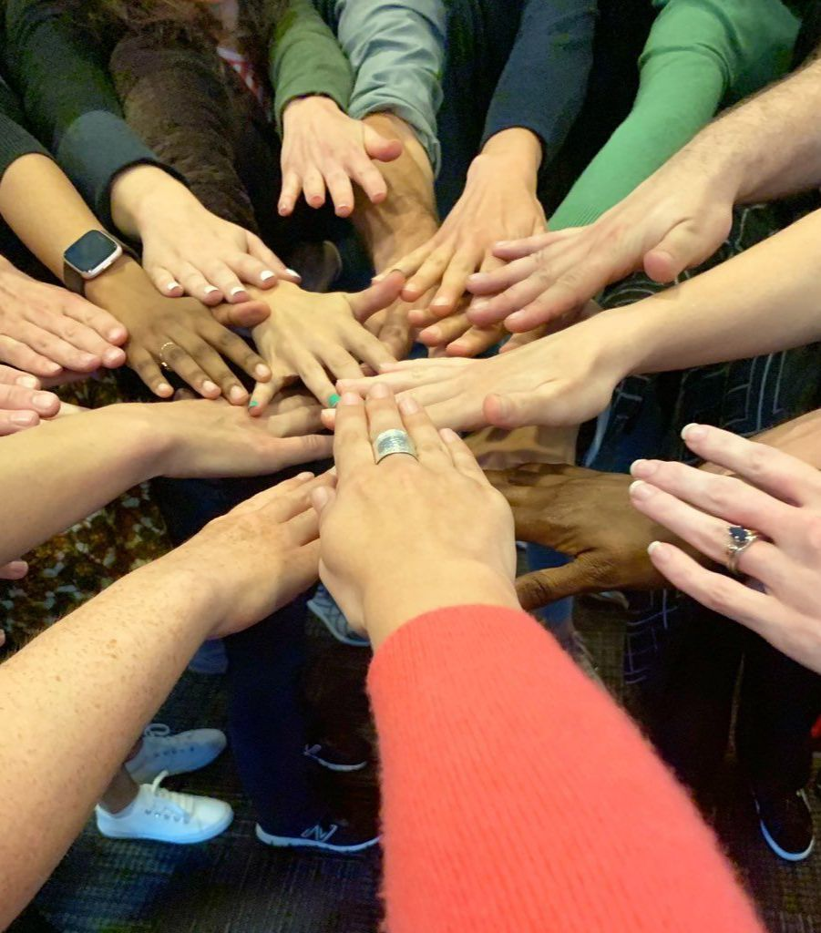 A group of hands together in a circle