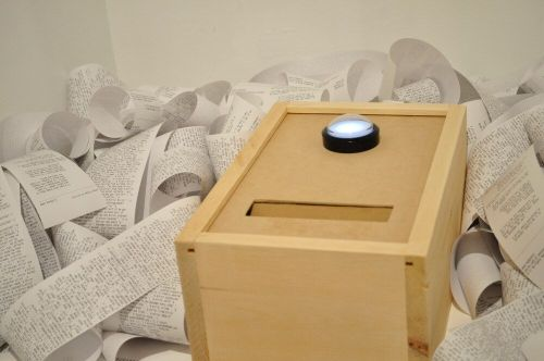 A plain wooden box with a slot and a large button on it, surrounded by receipt paper covered in text