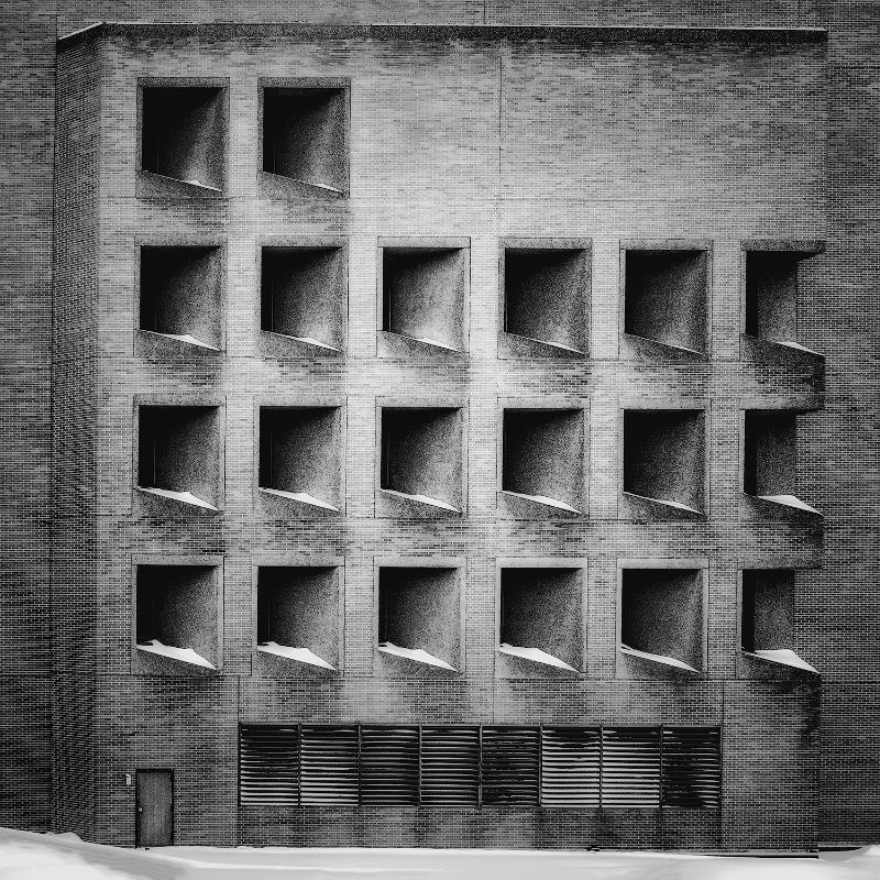 A stylized brick building full of tilted window openings