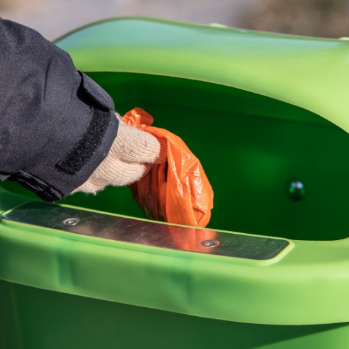Person disposing of garbage in a receptacle