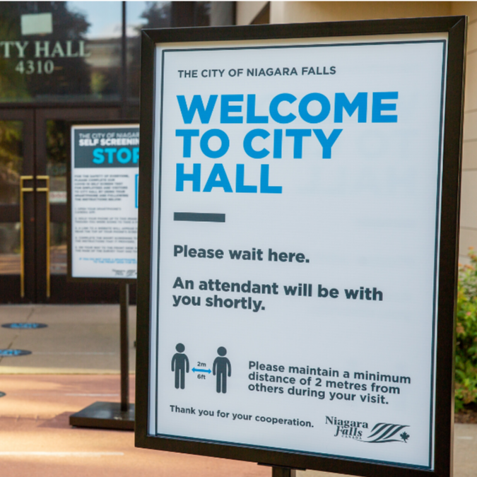 Welcome to City Hall sign, outside the doors.