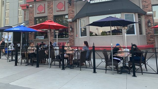 People sitting outside at a sidewalk patio.