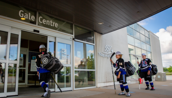 Hockey players, distanced, entering the Gale Centre arena