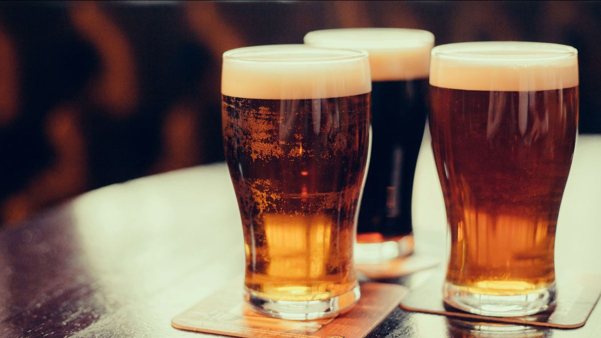 Three glasses of beer, sitting on a table.