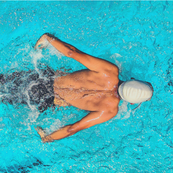 A man swims laps in a clear blue pool.