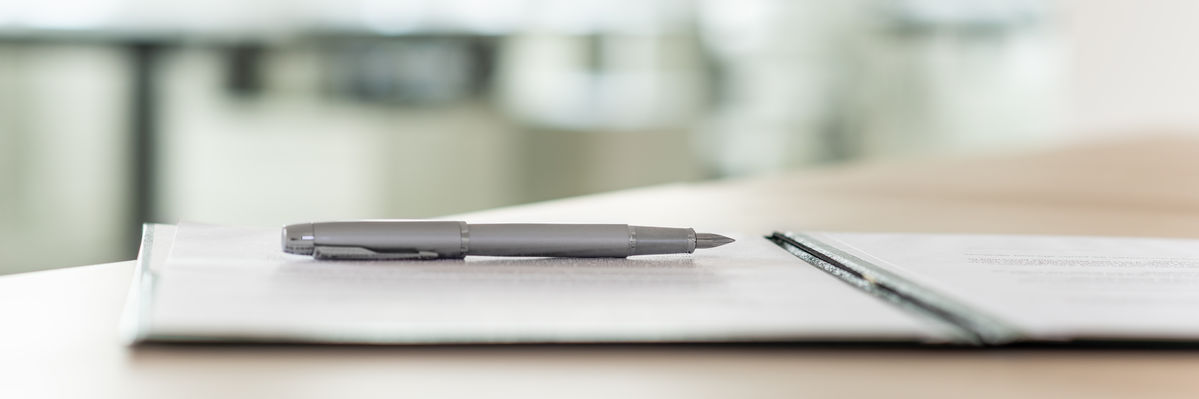 contract open on a desk, with a pen