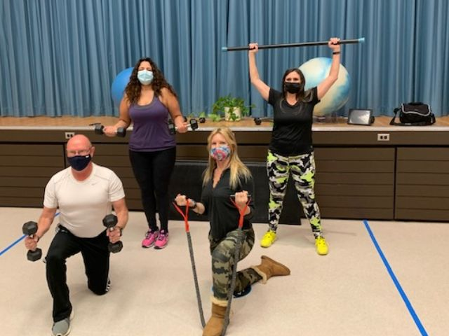"""Coronation Fitness Instructors pose together on our new """"set"""". They are wearing masks and lifting weights and other fitness equipment."""