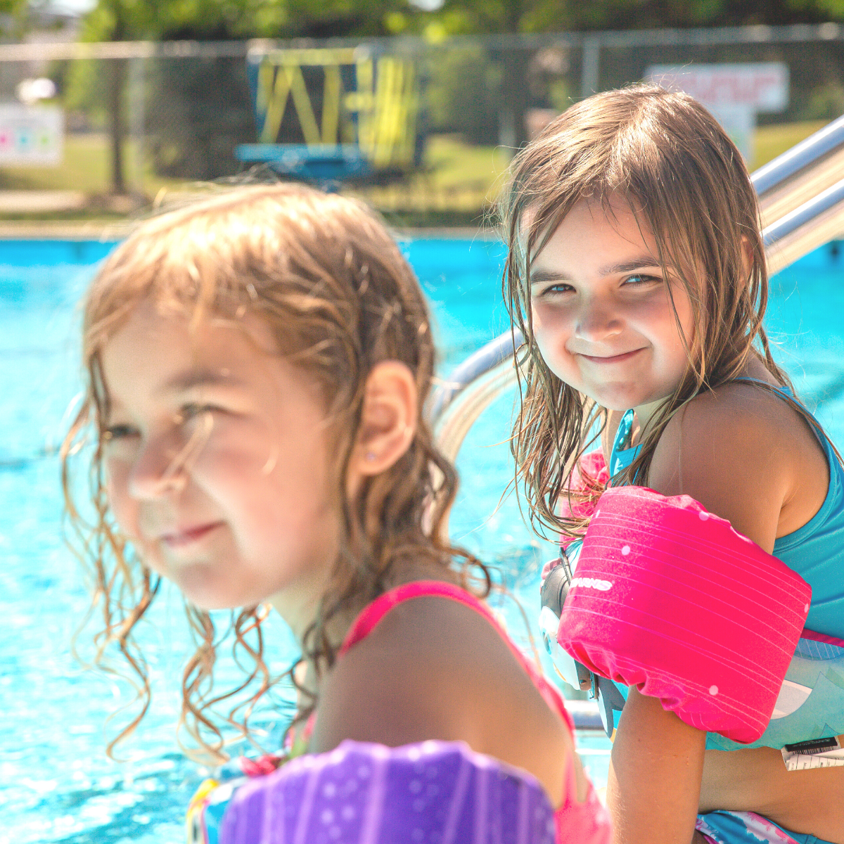 Two young girls sit by the pool on a sunny day.