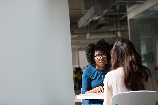 Two women sit at a table and engage in a dialogue