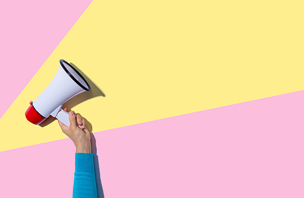 A hand holds up a megaphone against a yellow and pink backdrop