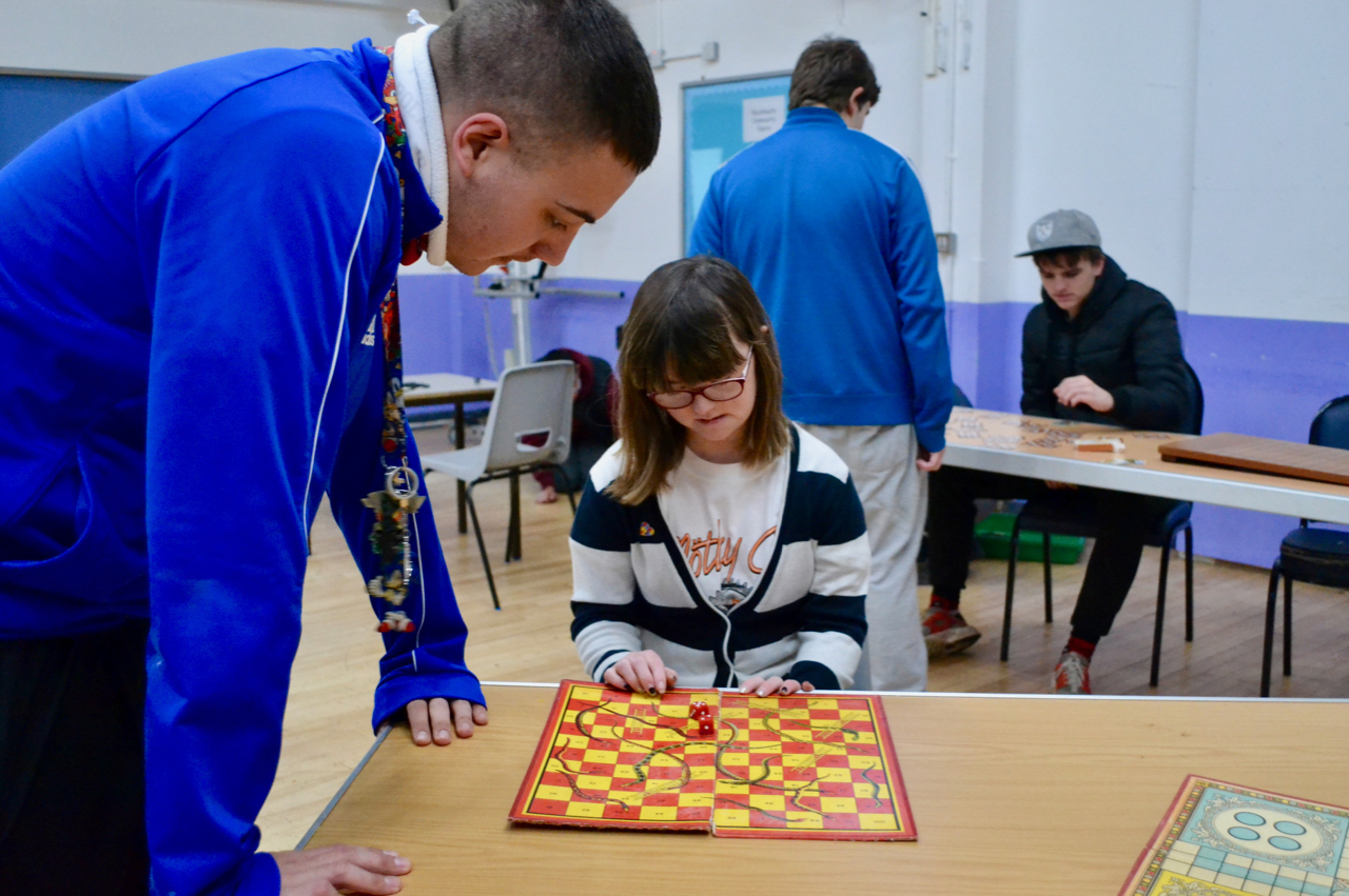 Two young people playing snakes and ladder