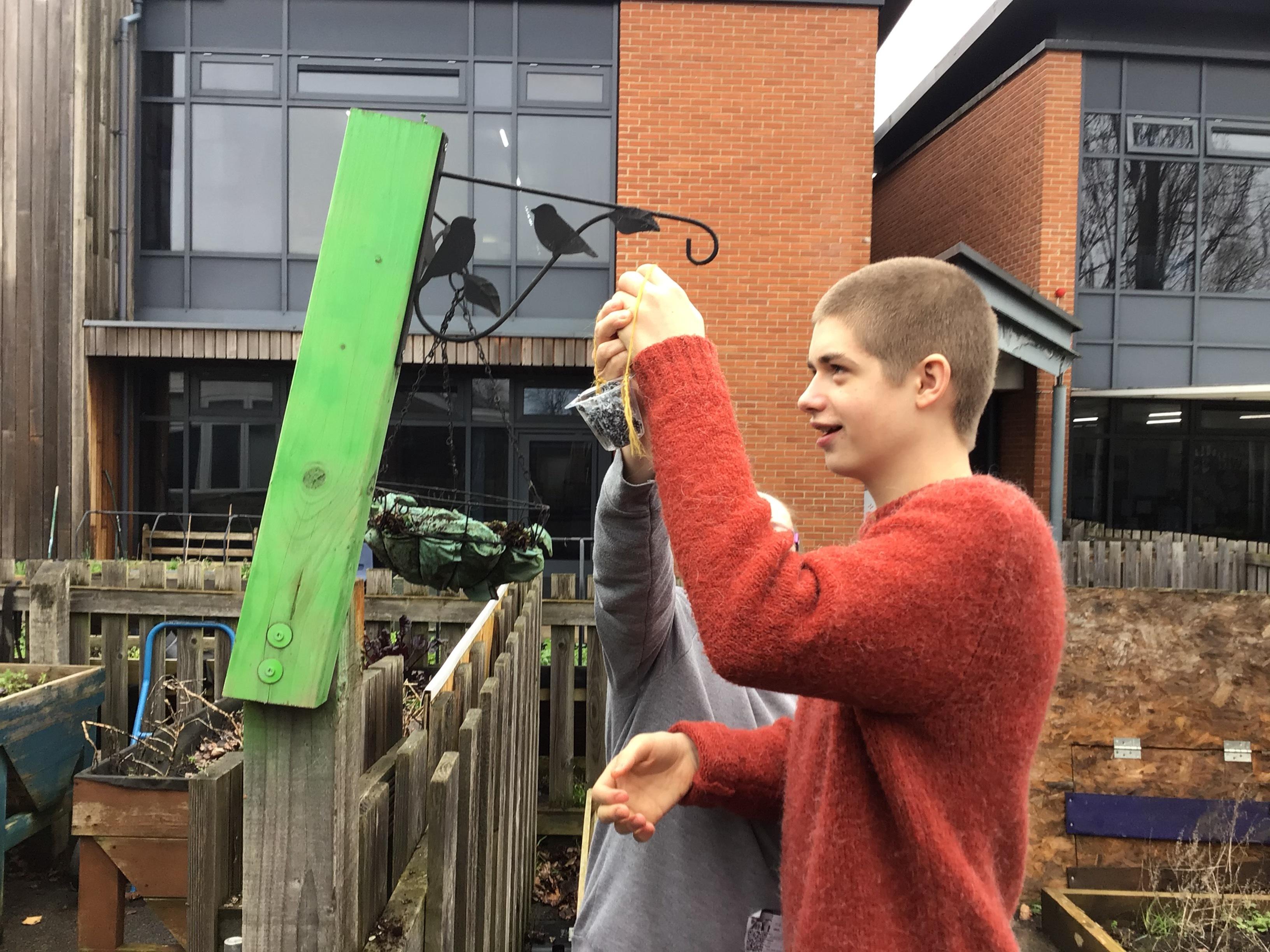 Student with teacher hanging up a bird feeder