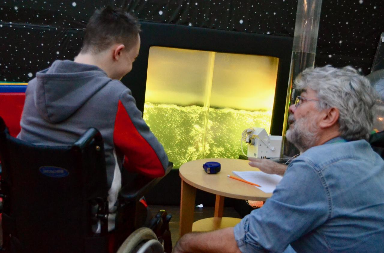 Man talking to boy in wheelchair