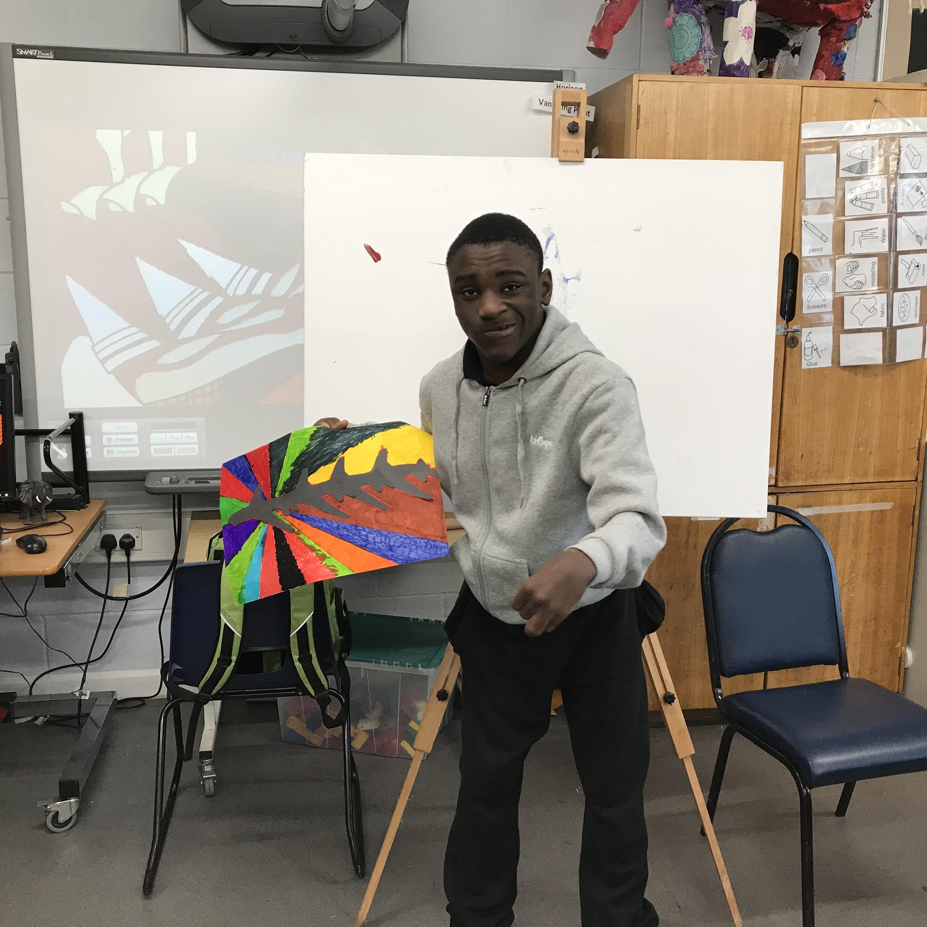 Student holding artwork up