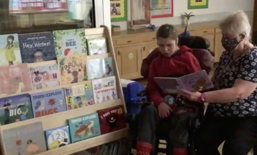 Image of a young girl in a wheelchair having a book read to her by her carer