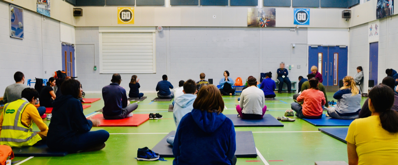 Students doing yoga in a sports hall