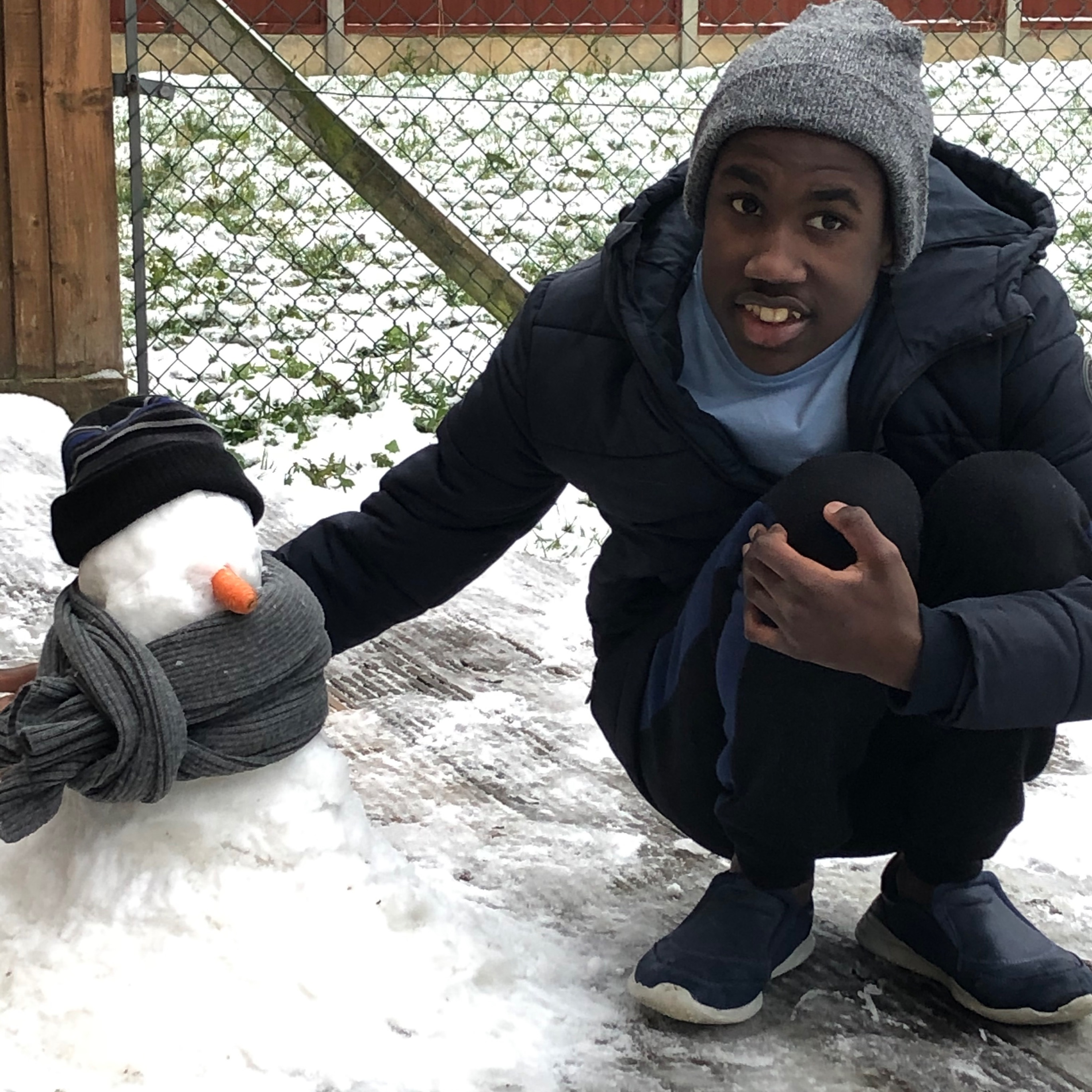 Young man in the snow next to a snow person