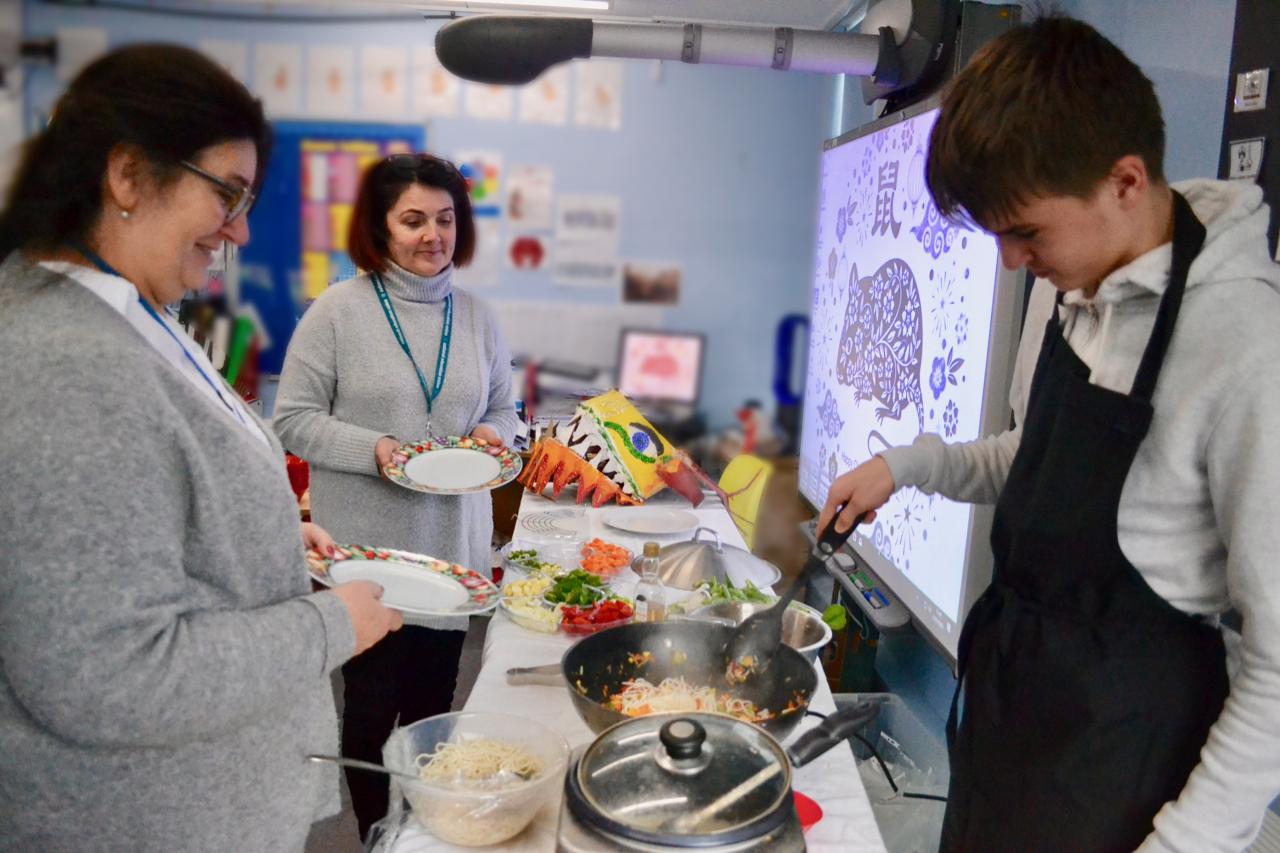 Boy serving vegetable noodles to staff