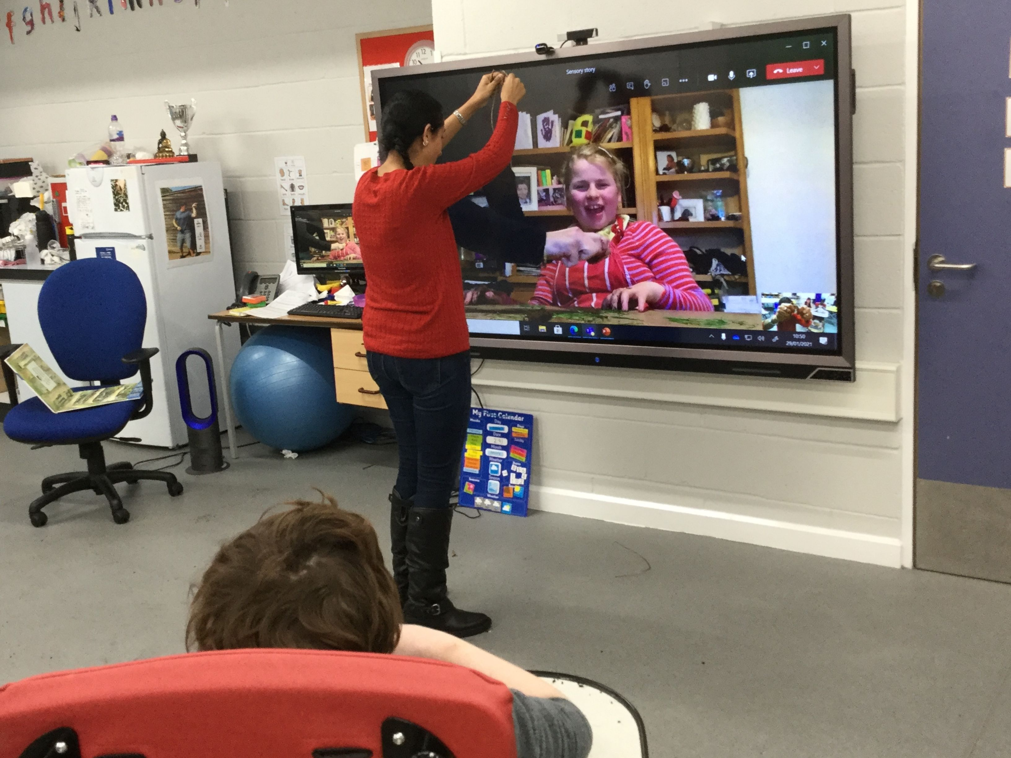 Class lesson with student on screen - a girl in pink top and boy in class in a wheelchair