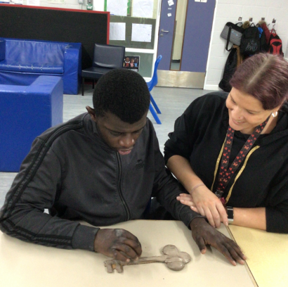Young man in trackshiut top at desk with teacher using clay to make a key