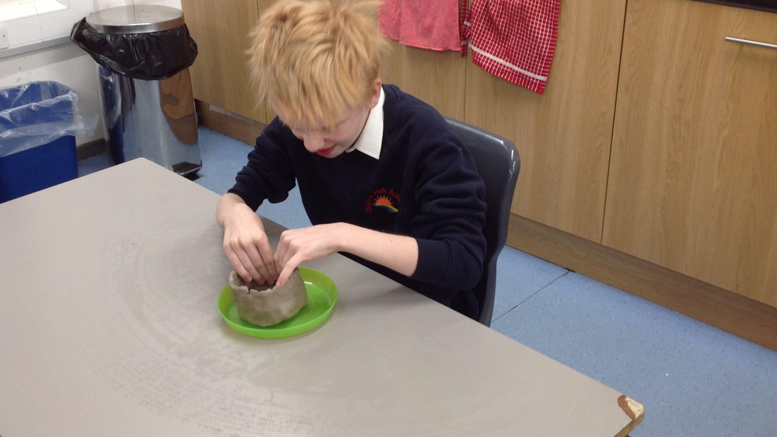 Young boy at desk making a clay pot