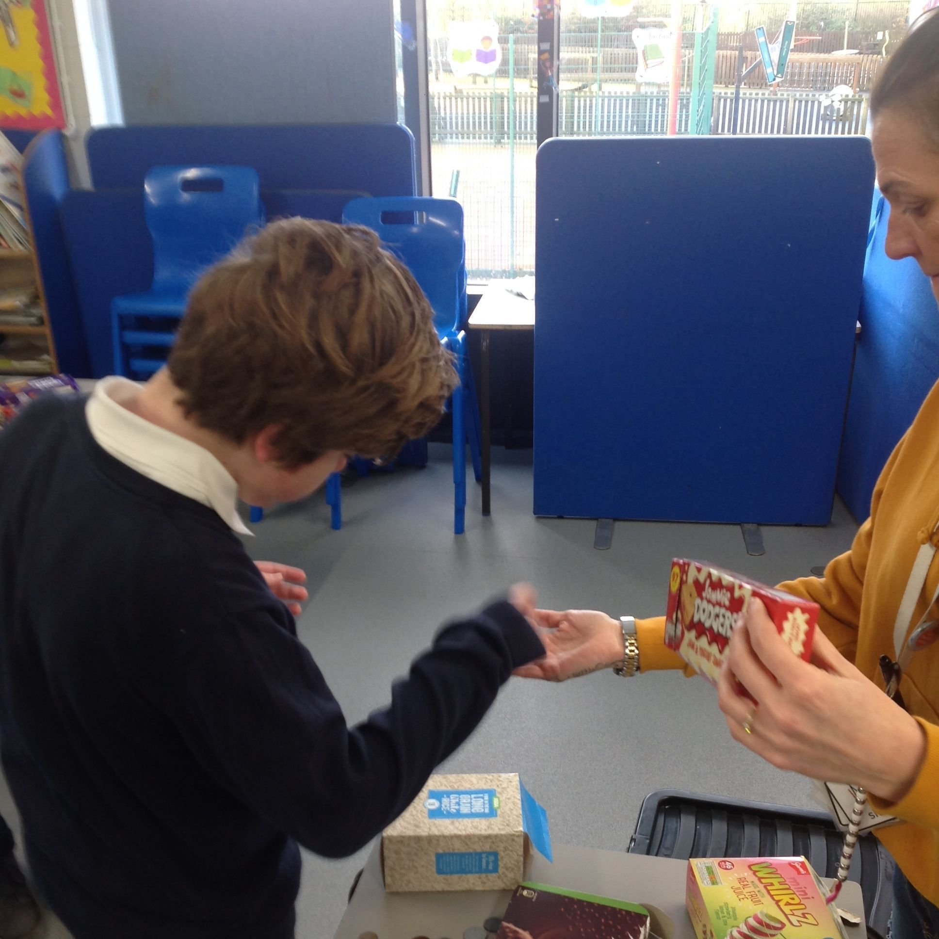 Young boy and teacher sharing items in a learning environment
