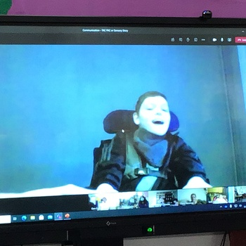 Young boy in wheelchair on a screen taking part in an online lesson