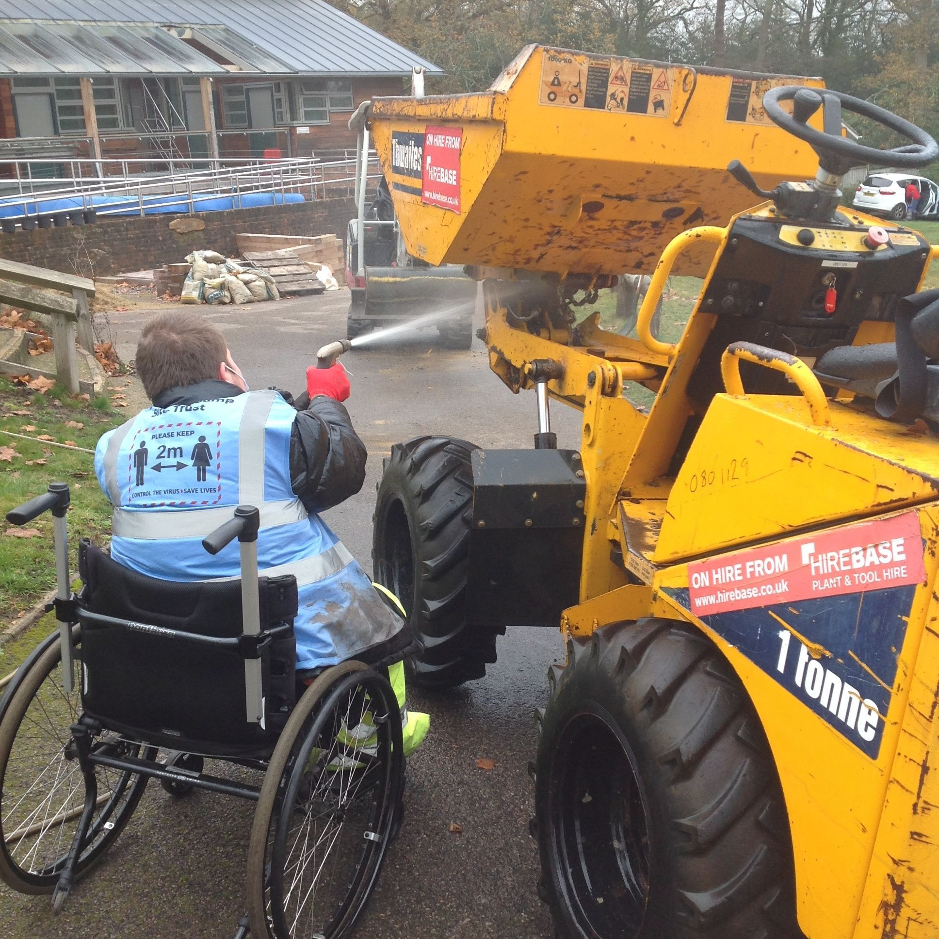 Young man in a wheelchair spraying a digger