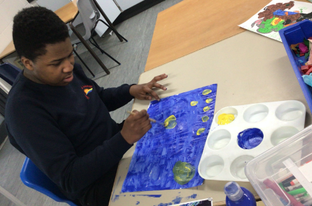 Young boy at desk painting a blue sky and yellow stars