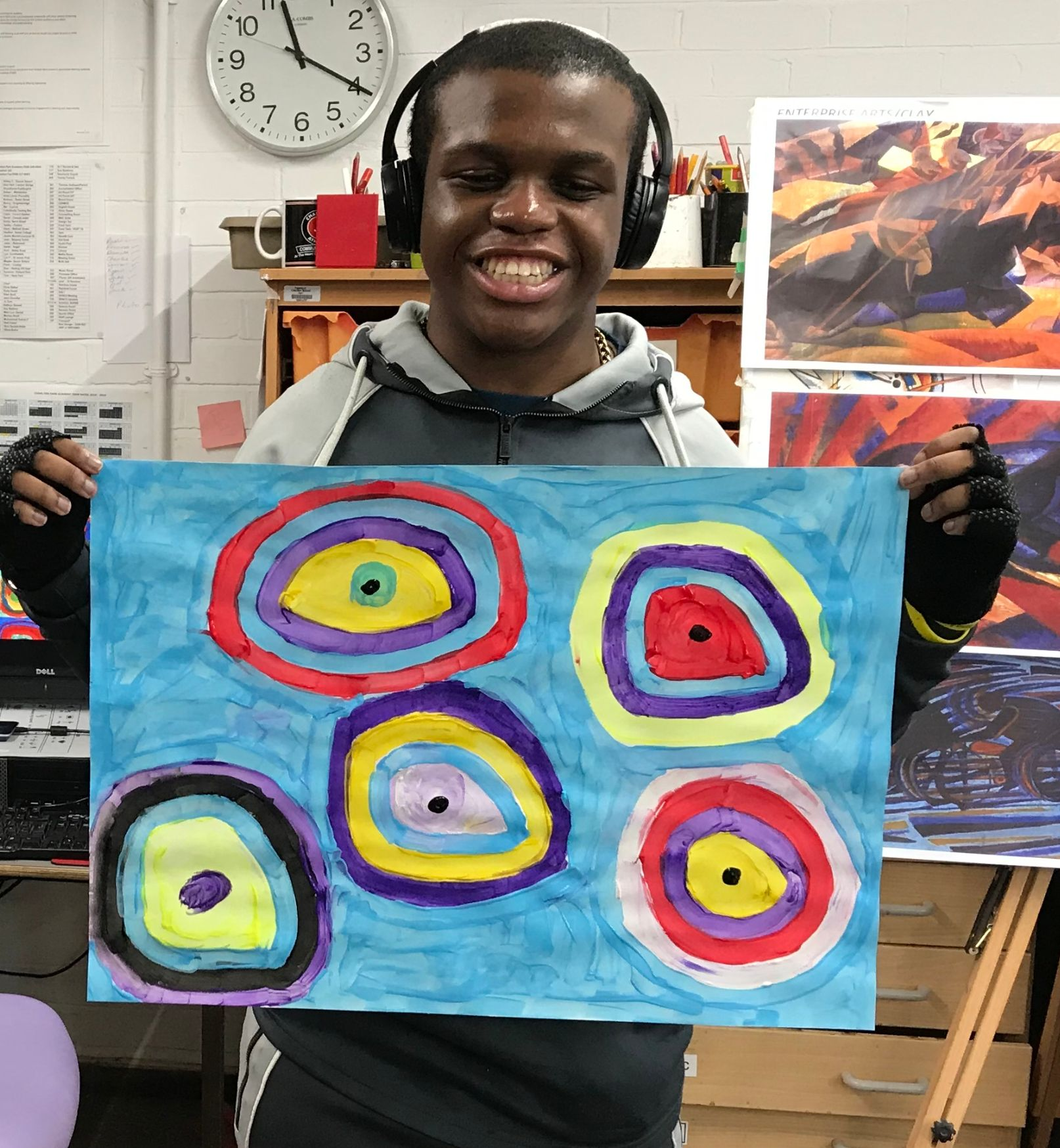 Young man holding up art work