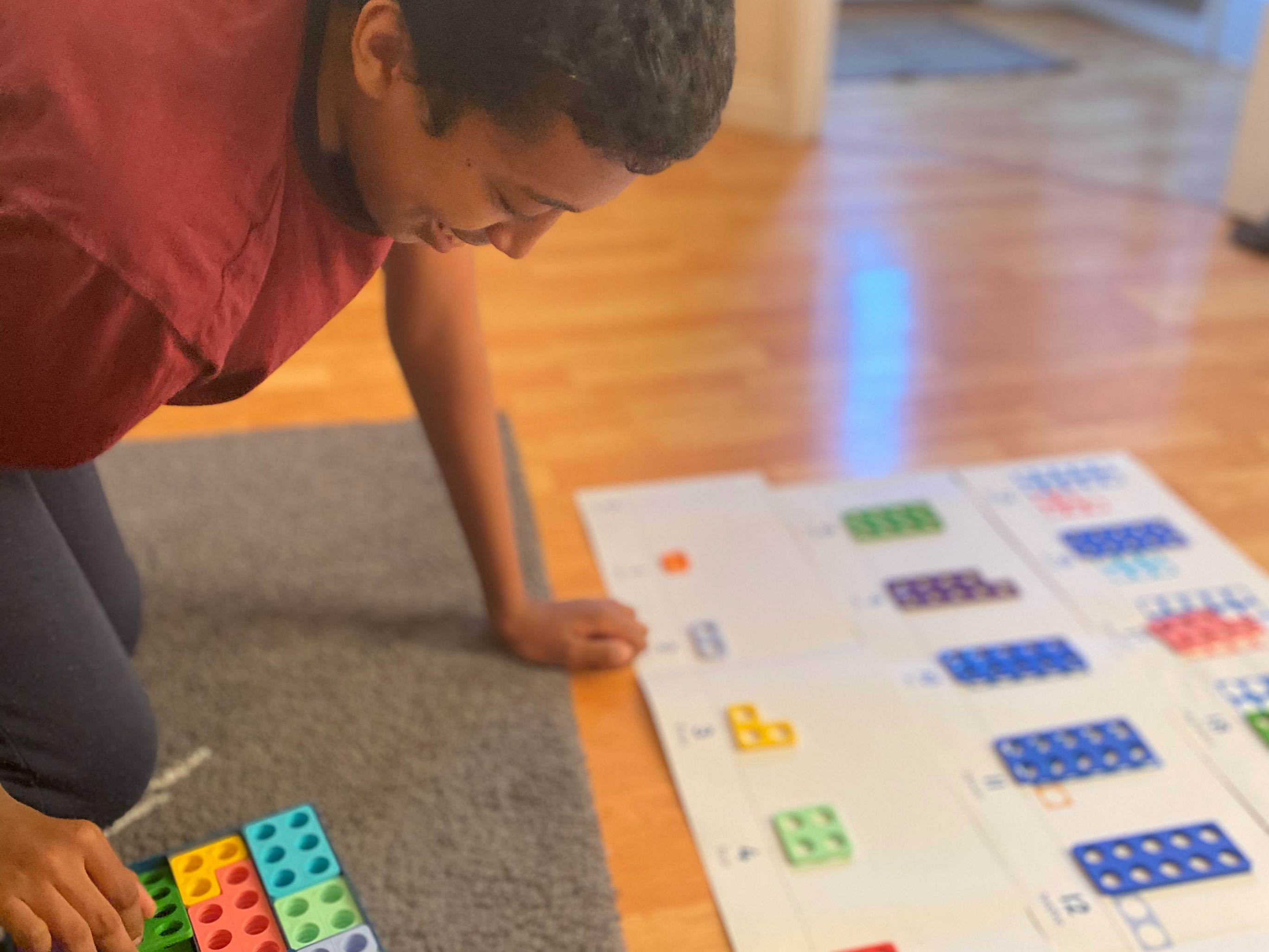 Boy on his knees using coloured blocks to do maths