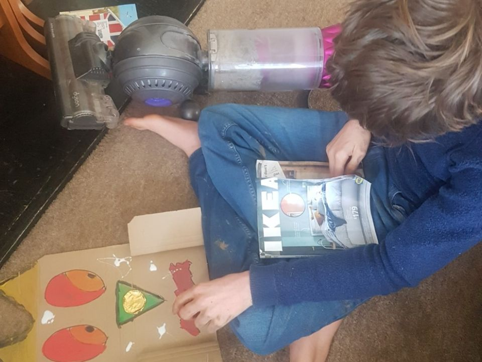 Image of a boy on the floor with an ikea catalogue and a painting
