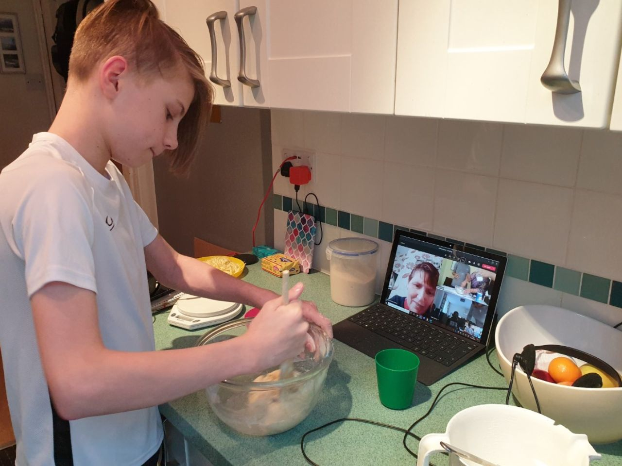 Boy cooking while following instructions from teacher online