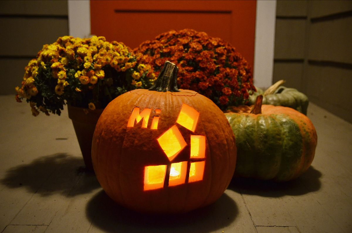 Pumpkin sitting on a porch that is carved with the Michigan UXPA logo