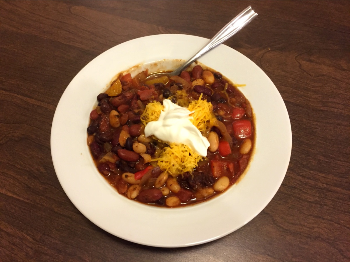 A white bowl full of bean chili topped with shredded cheese and a dollop of sour cream