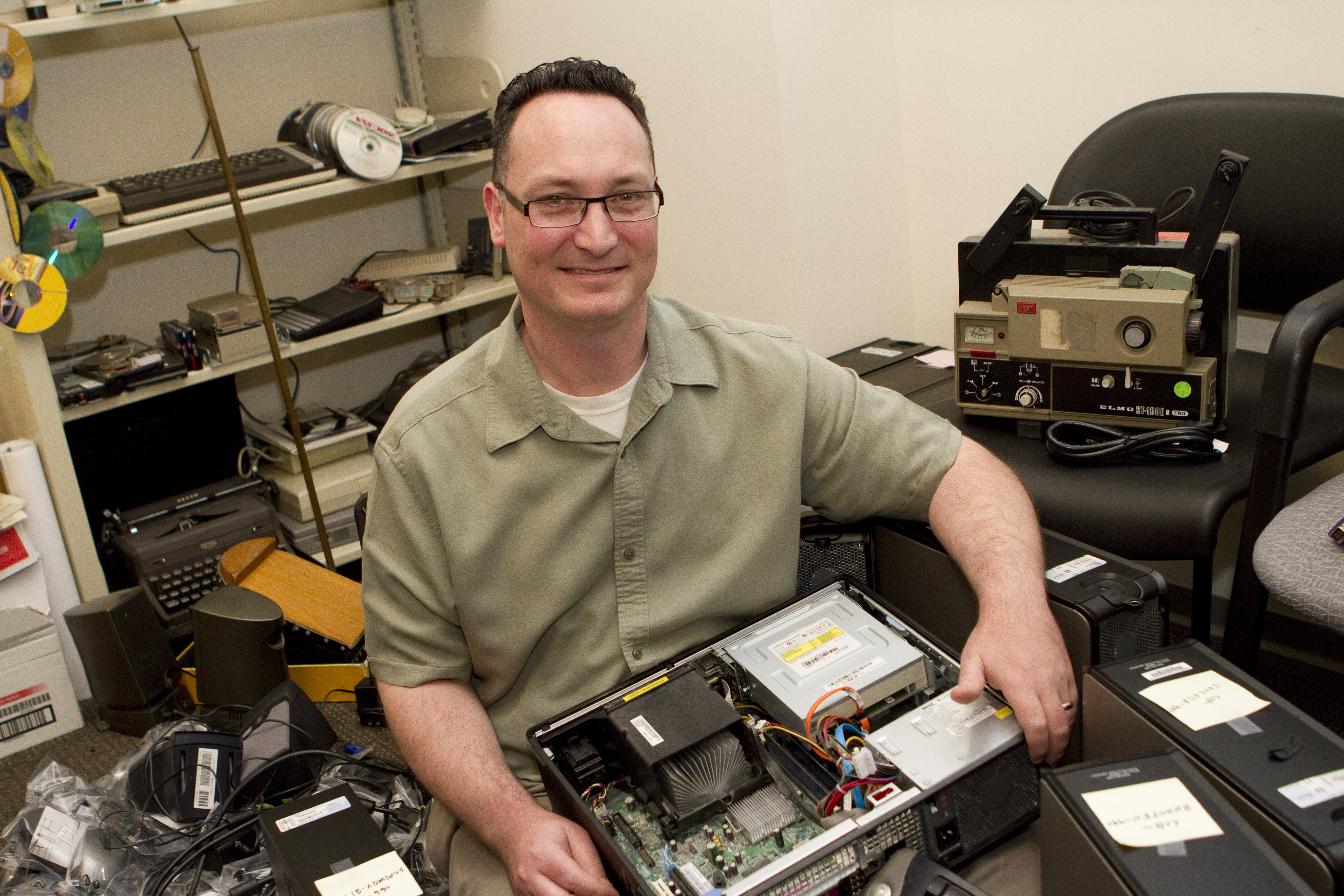 Photo of Brett Fisher with partially deconstructed computer, surrounded by assorted computing equipment