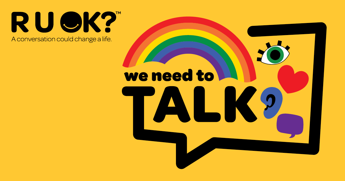 R U OK? logo with text we need to TALK inside a speech bubble. The speech bubble also contains icons for a rainbow, eye, heart, ear and speech bubble.
