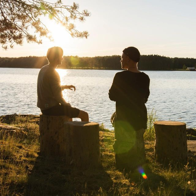 Two young men in conversation by a lake. They are sitting on logs and the sun is setting.