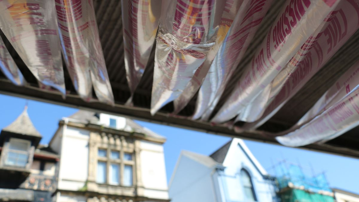 Close-up of 'Missing Live Theatre' ribbon installation under the Volcano canopy. Buildings opposite seen in distance.