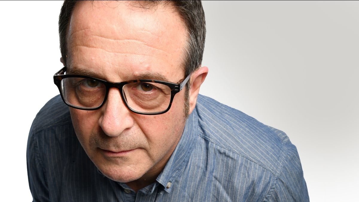 Mark Thomas leaning in to camera, wearing glasses.