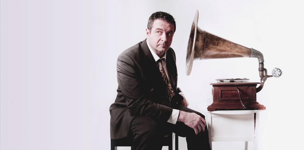 Picture of Mark Thomas listening to a gramophone.