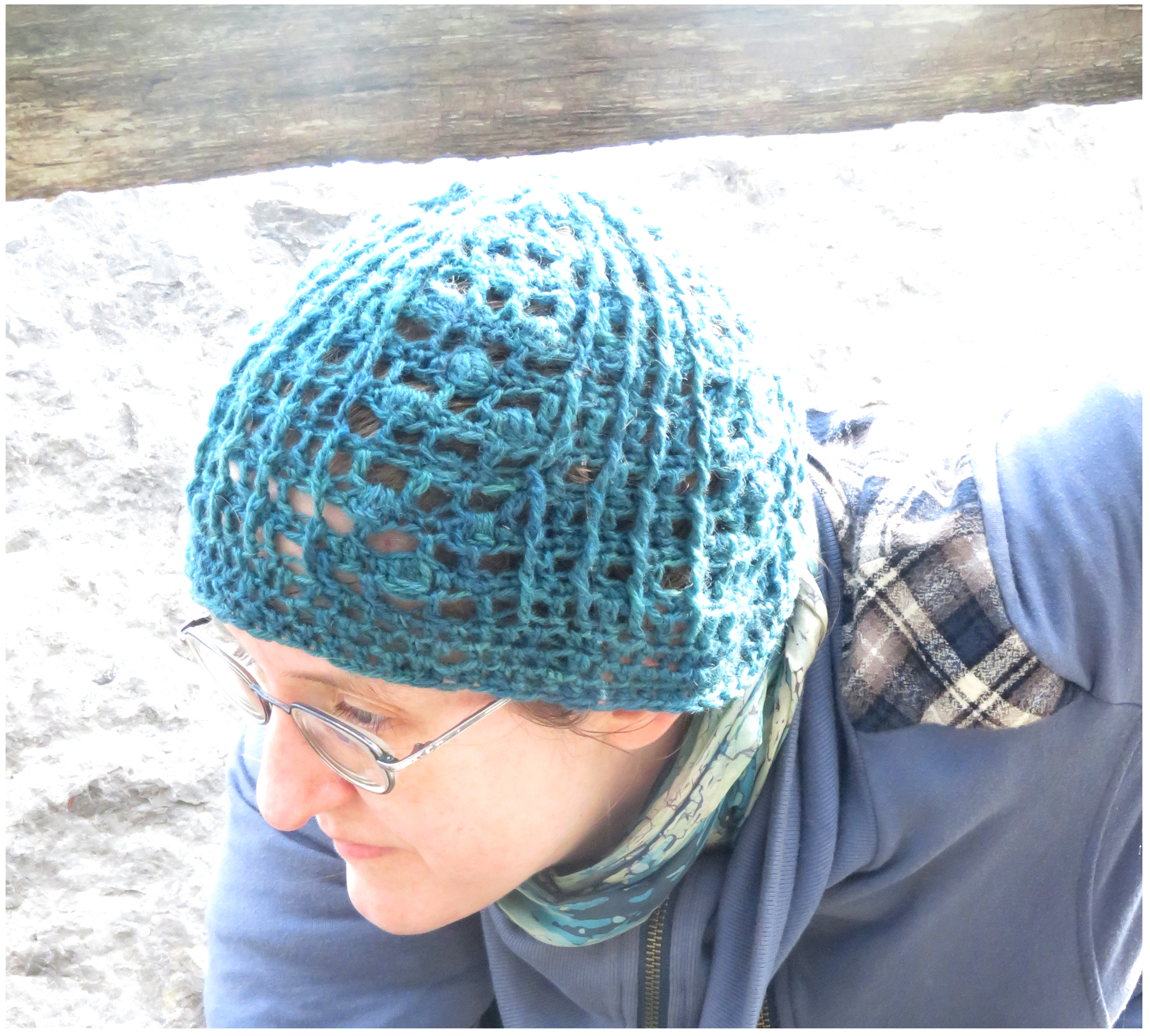 A woman wearing a crochet lace hat.  The hat is made in a dark teal yarn; with textured post stitches and crochet bobbles.