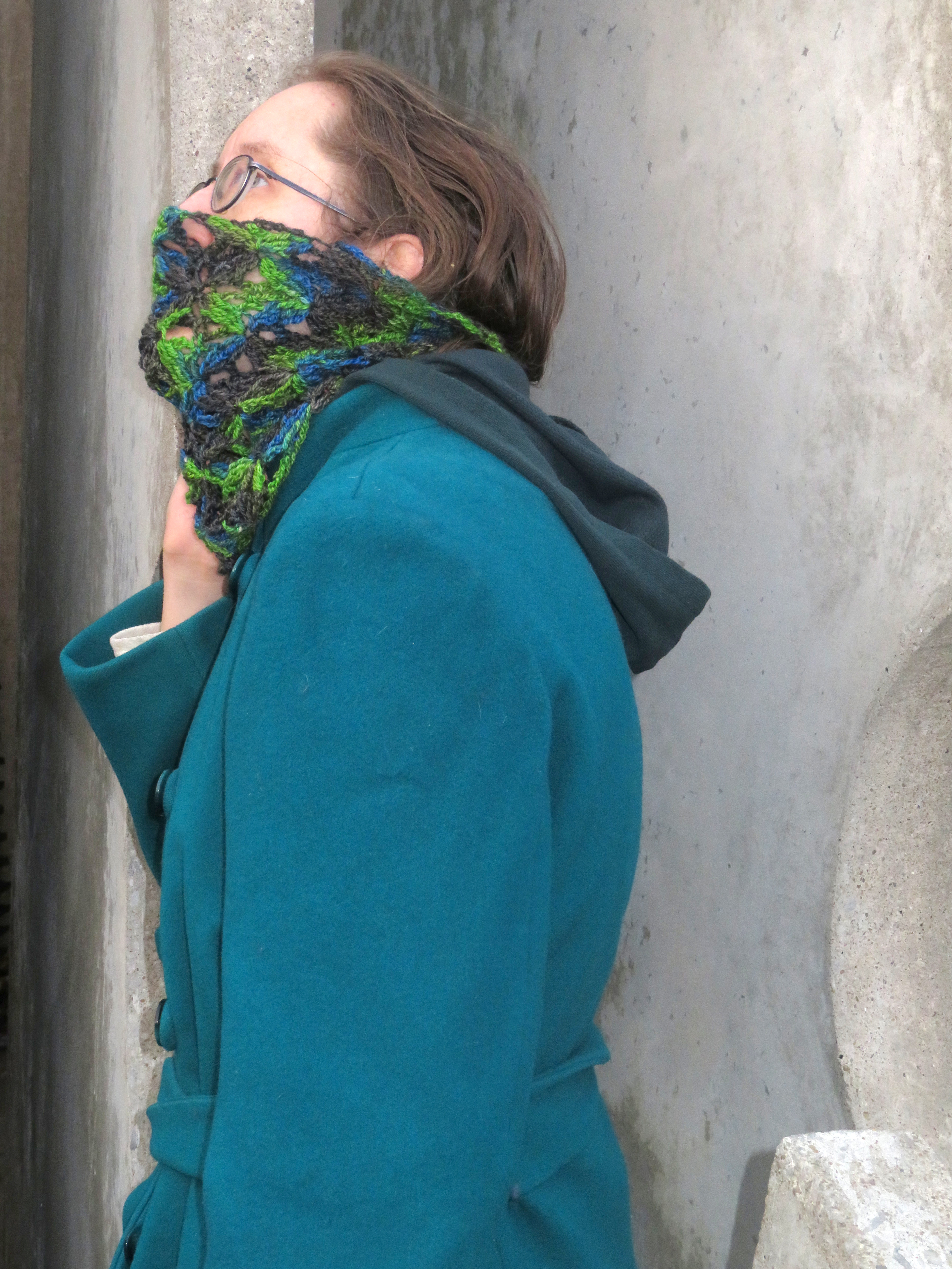 A woman wearing a crochet lace cowl done in a variegated yarn. The cowl is pulled up over her mouth and nose.