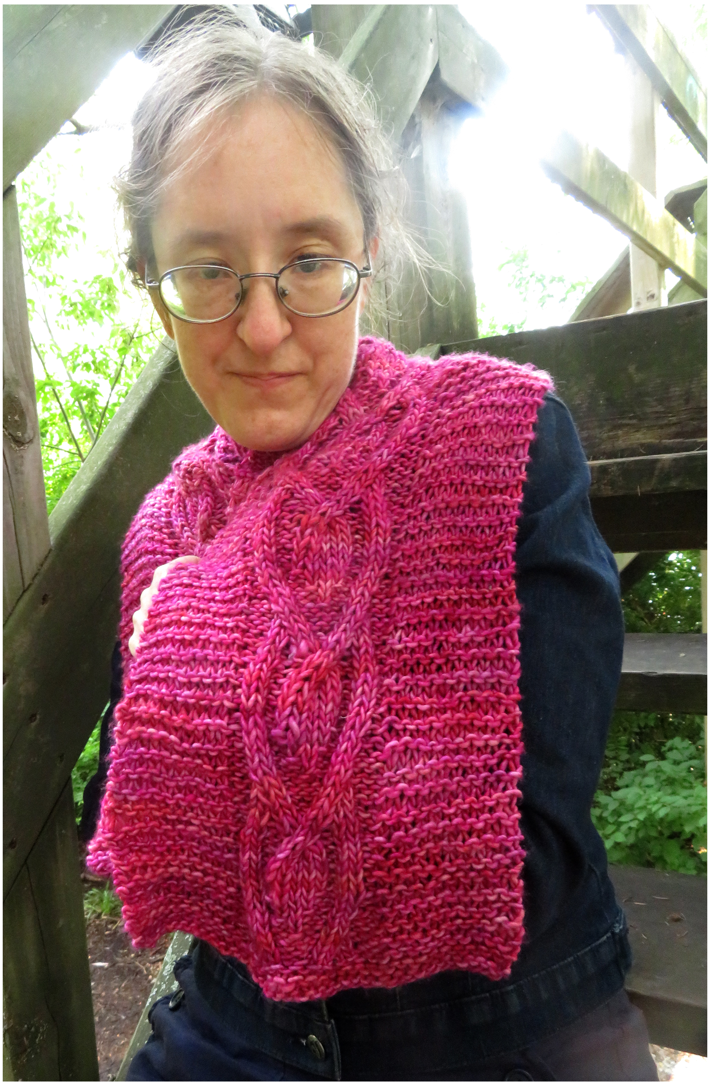 A woman wearing a deep pink cabled scarf knit in bulky  weight yarn.  The scarf is spread over one shoulder, and is done mostly in garter stitch with a large central cable.