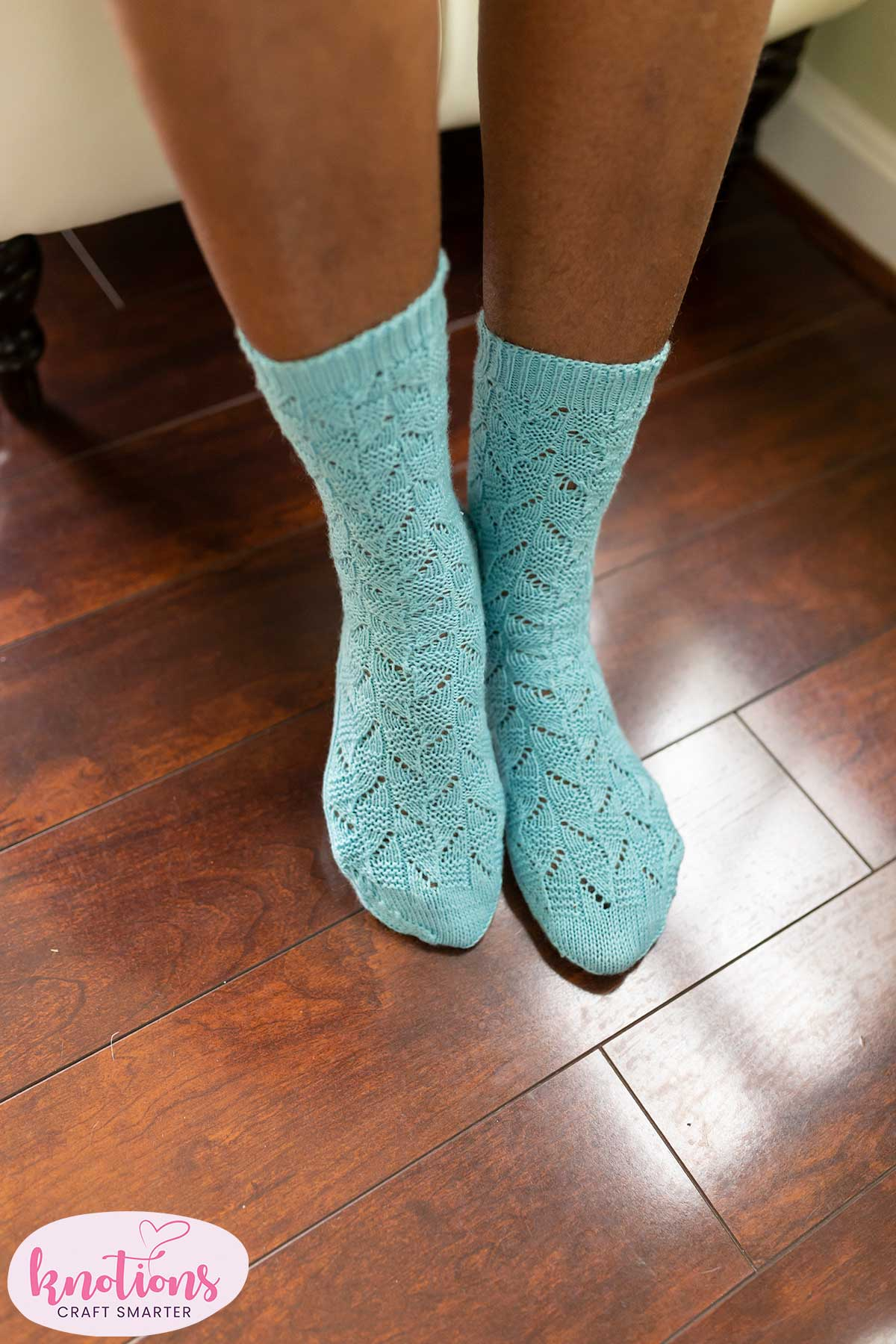 A person wearing a pair of pale blue fingering-weight lace socks