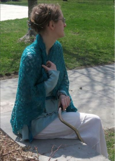 A woman wearing a large blue-green lace shawl. She is holding the shawl at her neck with one hand.