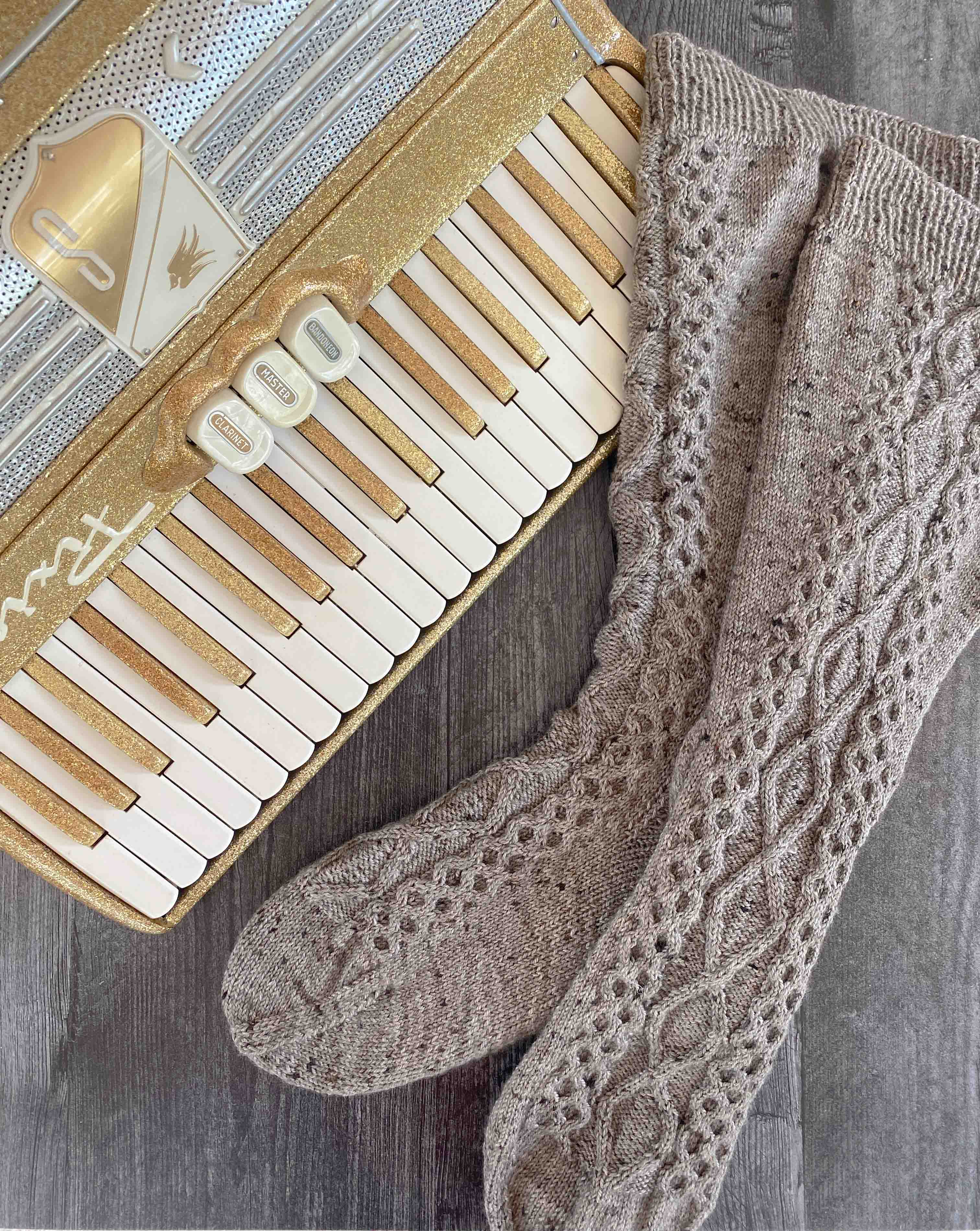 a pair of tall grey socks knit in fingering-weight yarn.  The socks have crossing cables on the leg and instep, and honeycomb cables on the side of the leg.